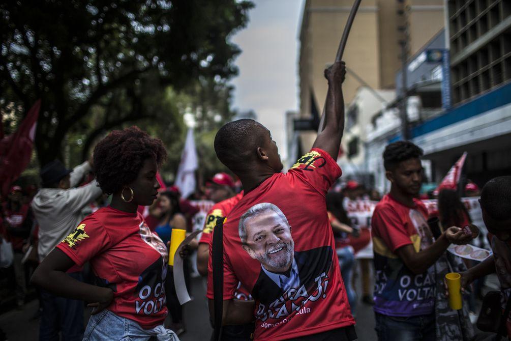 Demonstranten mit roten Lula-Shirts und Fahnen in den Strassen von Curitiba.