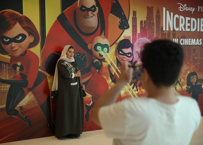 """Eine Frau lässt sich von ihrem Sohn vor einem Werbeplakat des Kinofilm """"Incredibles"""" fotografieren."""