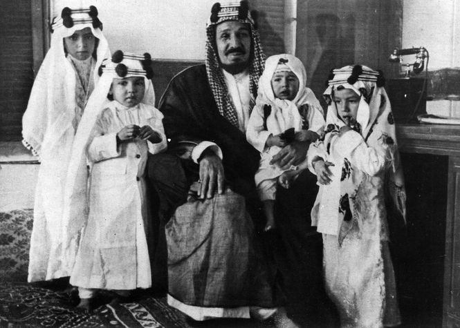 Historisch schwarz-weiss Fotografie zeigt den ersten König Saudiarabiens mit vier seiner Kinder.