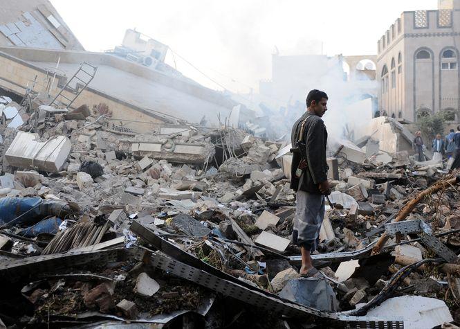 Ein Mann mit Gewehr steht auf den Trümmern eines komplett zerstörten Hauses.