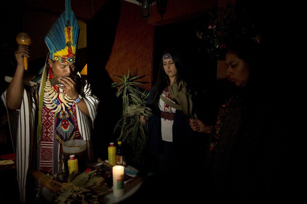 Ein Shaman mit Federkopfschmuck, Flöte und Rassel während der Ayahuasca-Zeremonie.