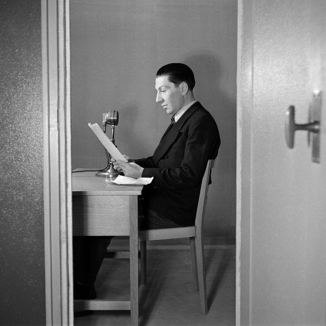 Ein Journalist sitzt in einem kleinen Raum vor einem Mikrofon und liest von einem Blatt
