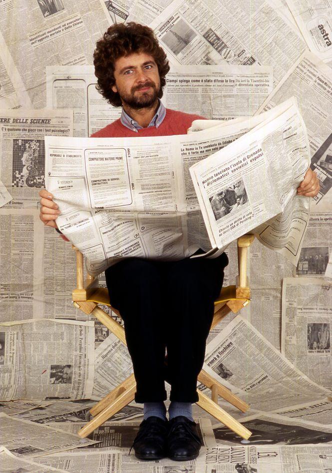 Grillo sitzend und Zeitung lesend vor einer Wand, die ganz mit Zeitungen zugeklebt ist