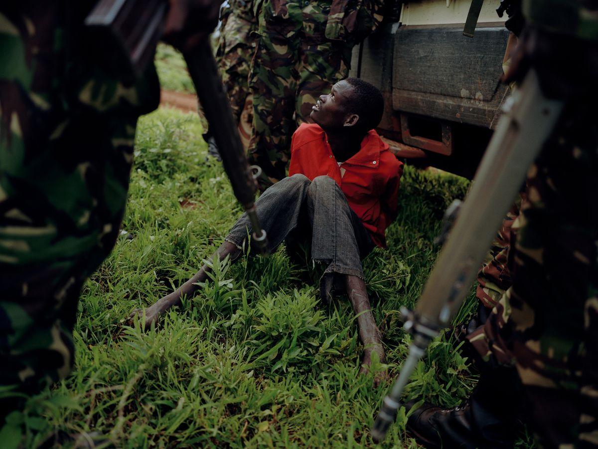 ein Wilderer sitzt mit gefesselten Armen am Boden, umringt von Rangern mit Waffen