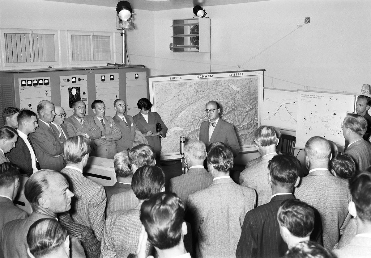 eine Gruppe Männer vor einer Schweizer Landkarte