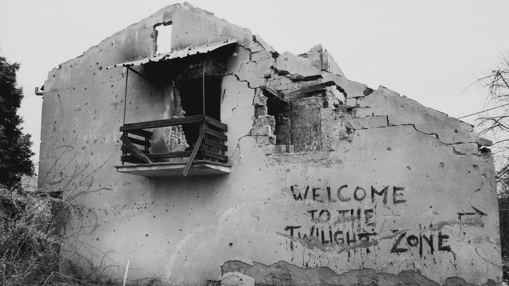"""Ein vom Krieg zerstörtes Haus. An der Fassada ein Graffiti """"Welcome to the Twilight Zone"""""""