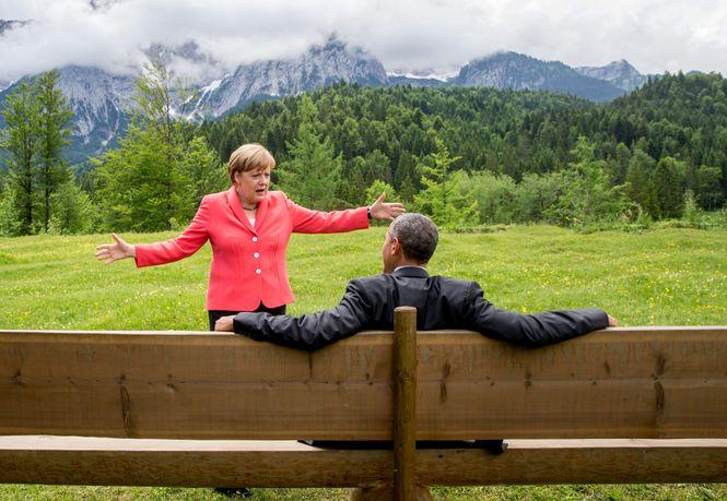 Merkel steht gestikulierend vor Obama, der auf einer Bank sitzt. Bergpanorama im Hintergrund