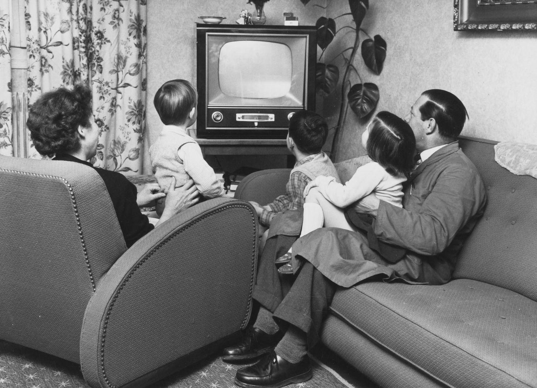 eine Familie im Wohnzimmer vor dem Fernsehen
