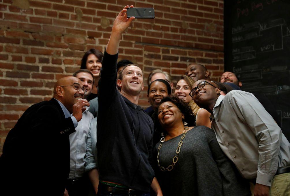 Mark Zuckerberg steht inmitten einer Gruppe von lächelnden Menschen und macht mit ihnen ein Selfie